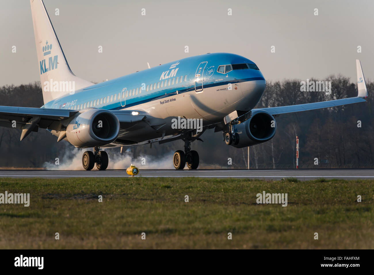 Landing Boeing 737 passenger aircraft of KLM with smoking tires at Zurich Kloten airport. - Stock Image