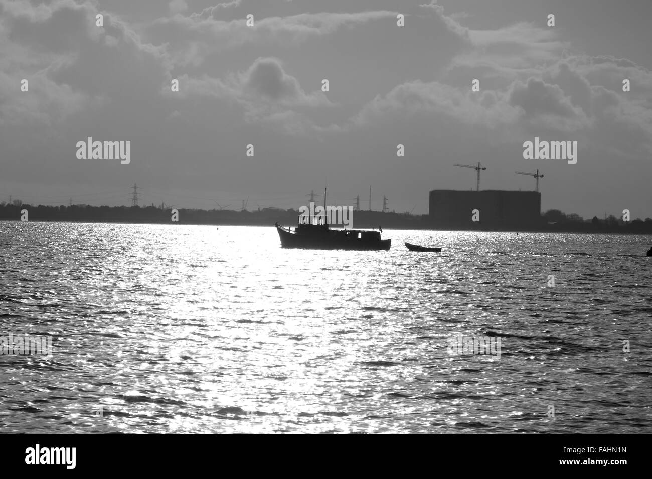A small fishing boat in silhouette and black and white sailing in front of Bradwell power station - Stock Image