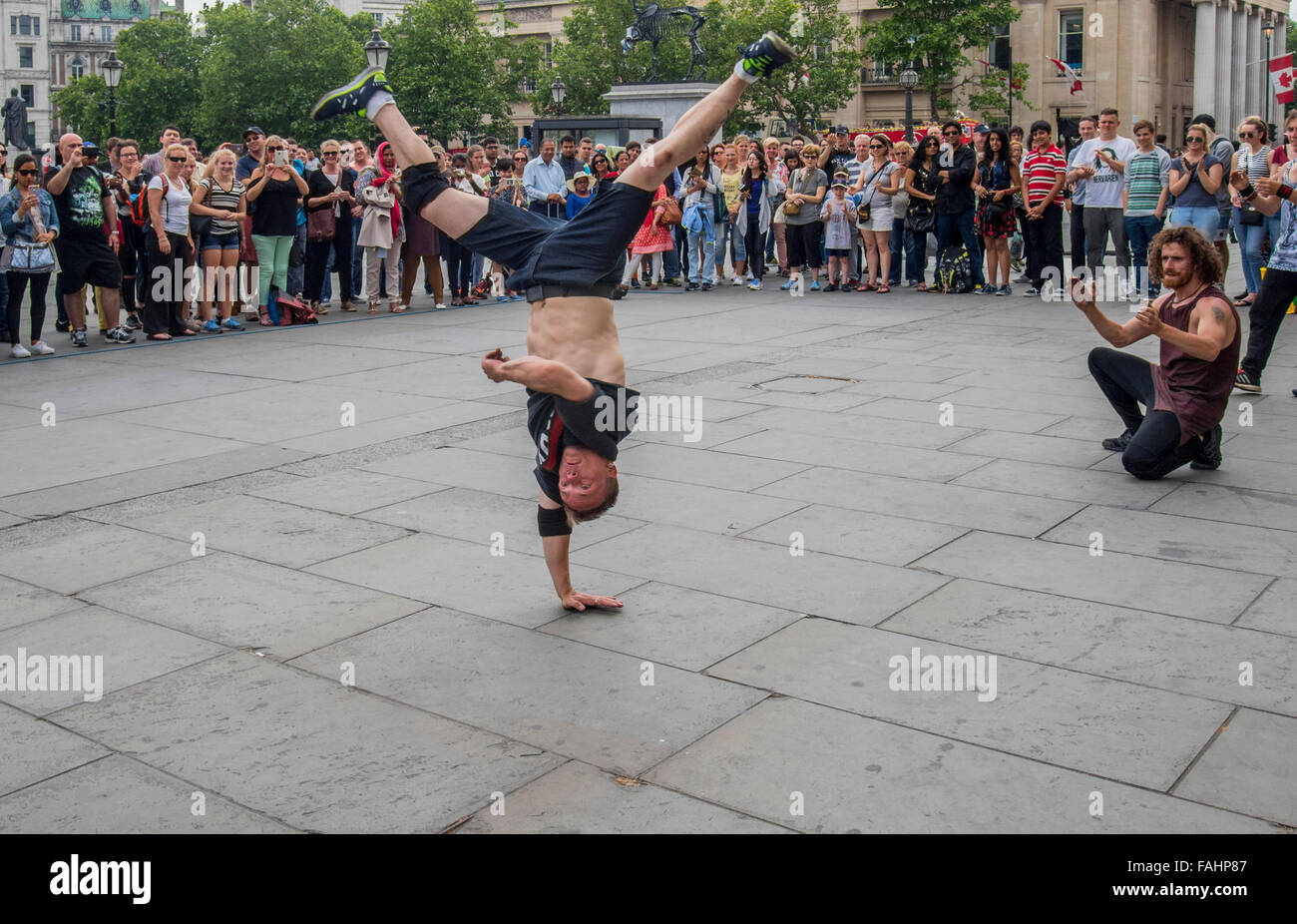 Street entertainers performing gymnastic feats for tourist and visitors inTrafalgar Square London England - Stock Image