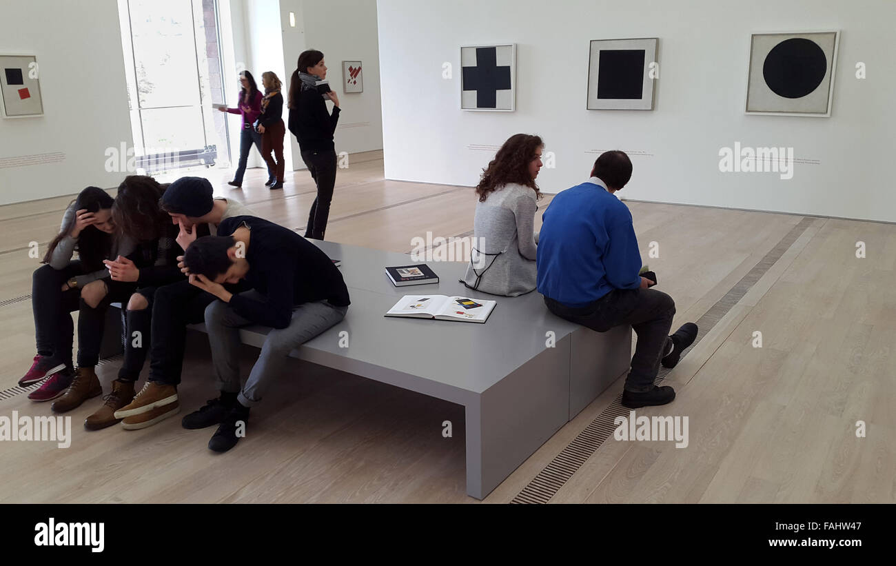 Visitors in front of the Suprematist paintings Black Cross (1915), Black Square (1929) and Black Circle (1915) by - Stock Image