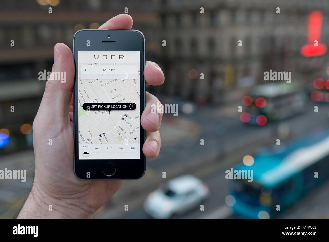 A man uses the Uber taxi smartphone app while stood in a tall building overlooking a busy city street (Editorial - Stock Image