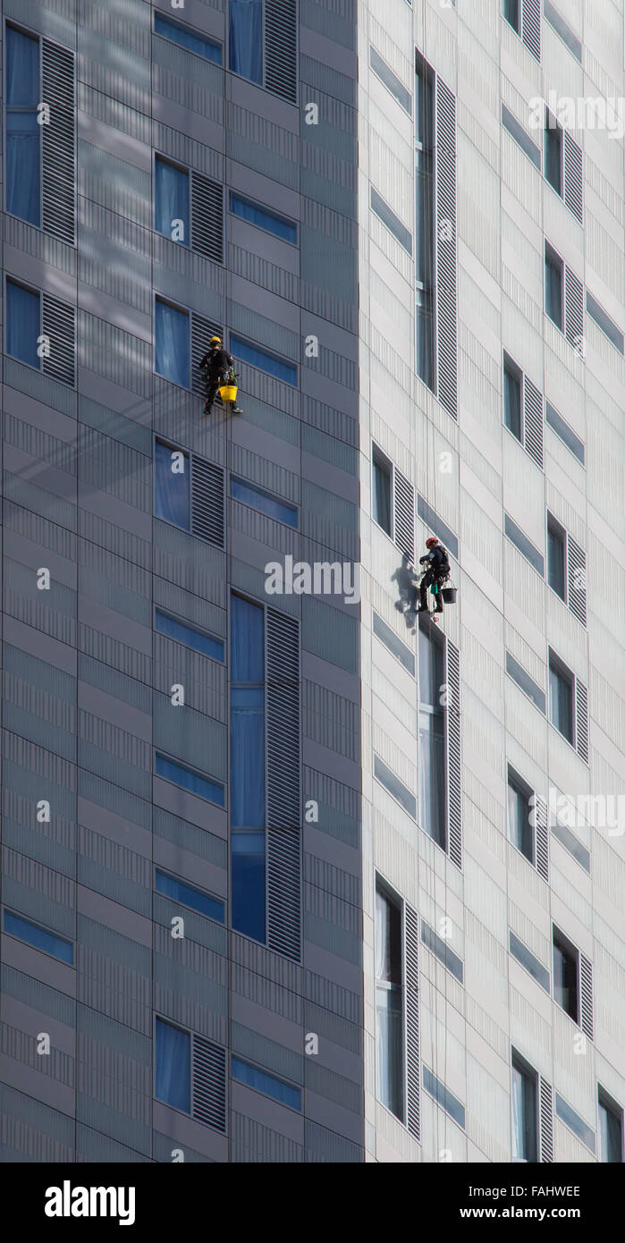 Abseiling window cleaners hard at work on a building in the East End of London UK Stock Photo