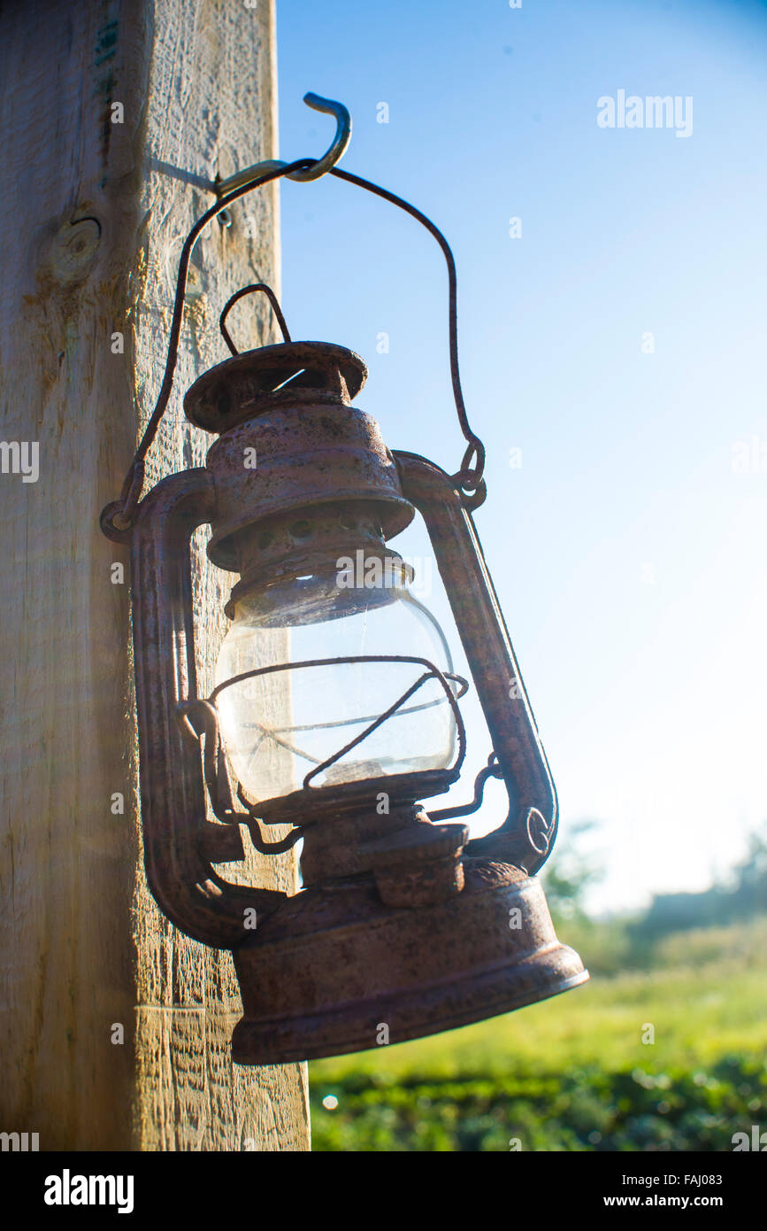 Old rustic kerosene lamp hanging from a post outdoors - Stock Image
