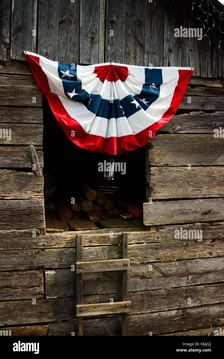 American flag colors drape a window of a crib barn displayed for July 4th independence celebrations in North Georgia, - Stock Image