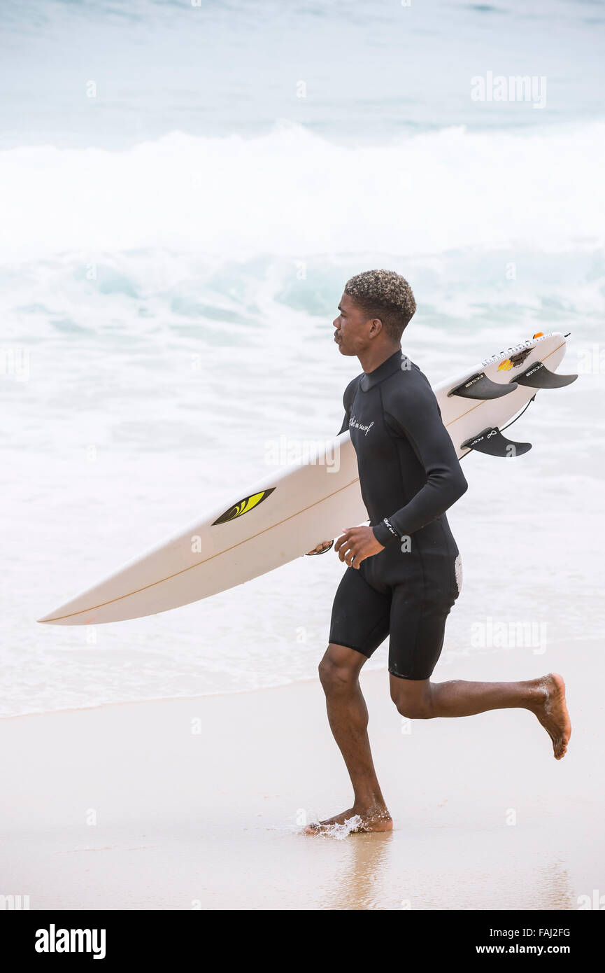 RIO DE JANEIRO, BRAZIL - OCTOBER 22, 2015: Brazilian surfer runs on the shore of Praia do Diabo at Arpoador near - Stock Image