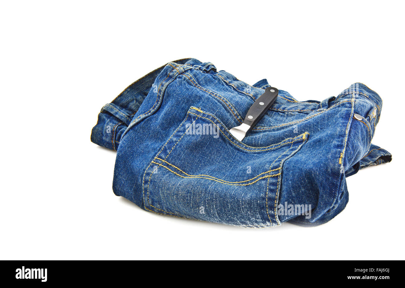 Blue jeans pocket with kitchen knife on white background - Stock Image