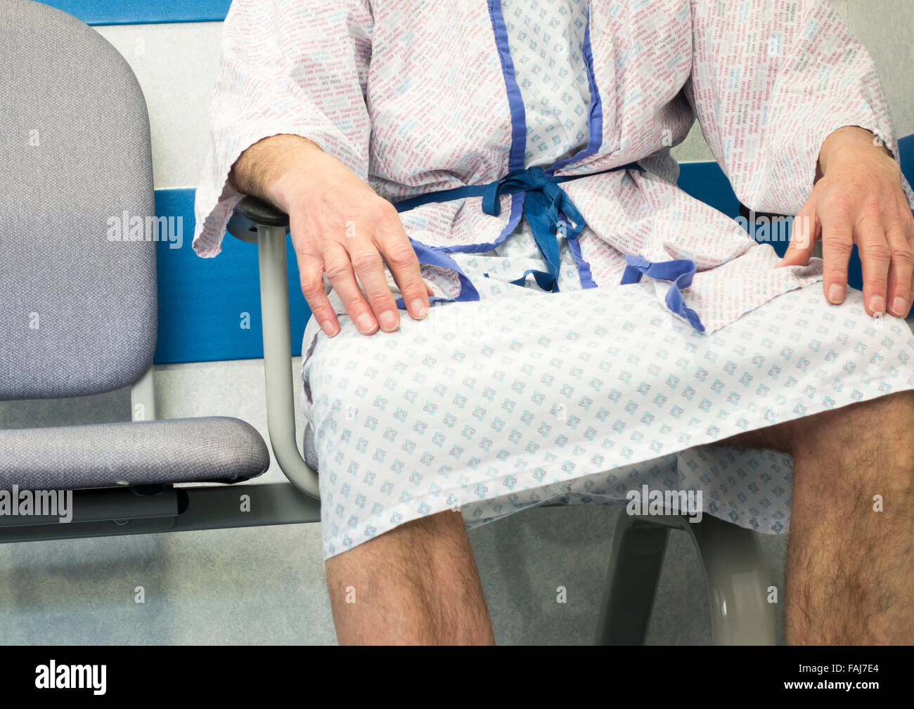 Man wearing hospital gown waiting to be taken to day surgery unit in NHS hospital. UK - Stock Image
