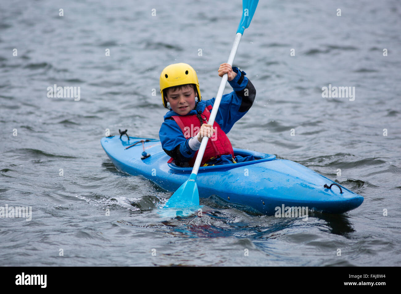 Boy Paddles in Kayak on Lake - Stock Image