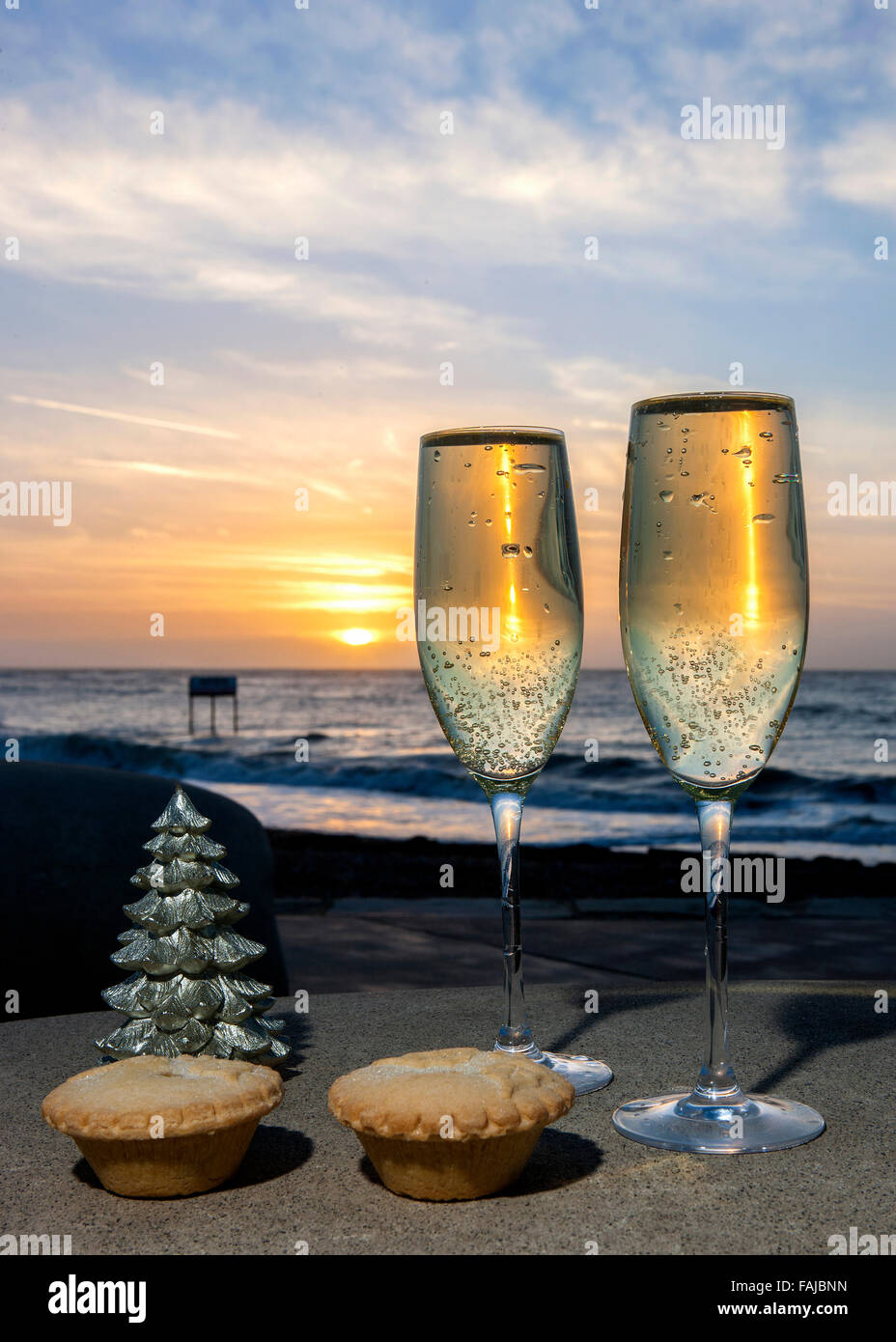 Champagne mince pies at Christmas by sea at sunrise - Stock Image
