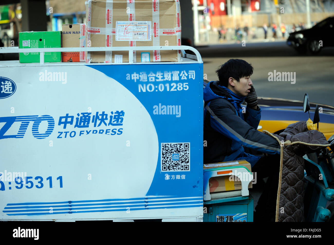 An electric tricycle for online-shopping express delivery shuttles in the street in Beijing, China. - Stock Image