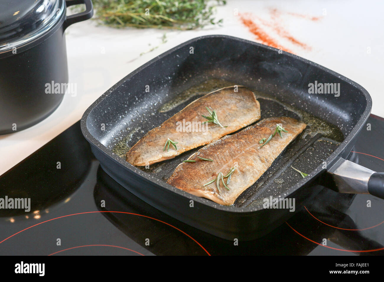Frying fish on an electric stove - Stock Image