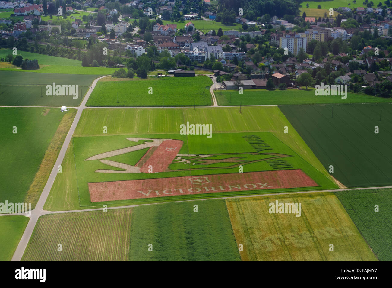 Aerial image of a super-size Victorinox Swiss army knife advertisement in a crop field. - Stock Image