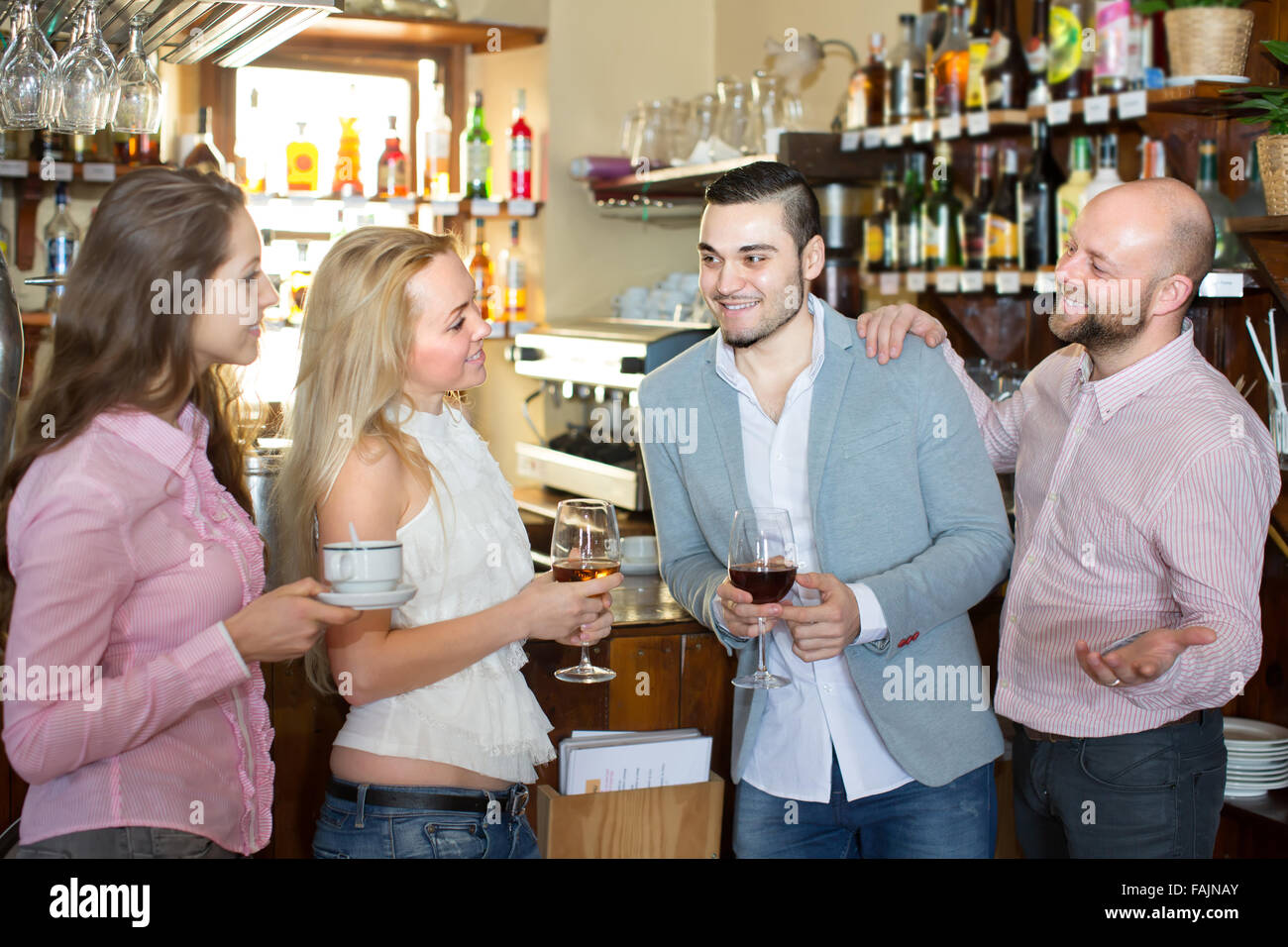 Casual acquaintance of young happy adults at bar. Selective focus - Stock Image