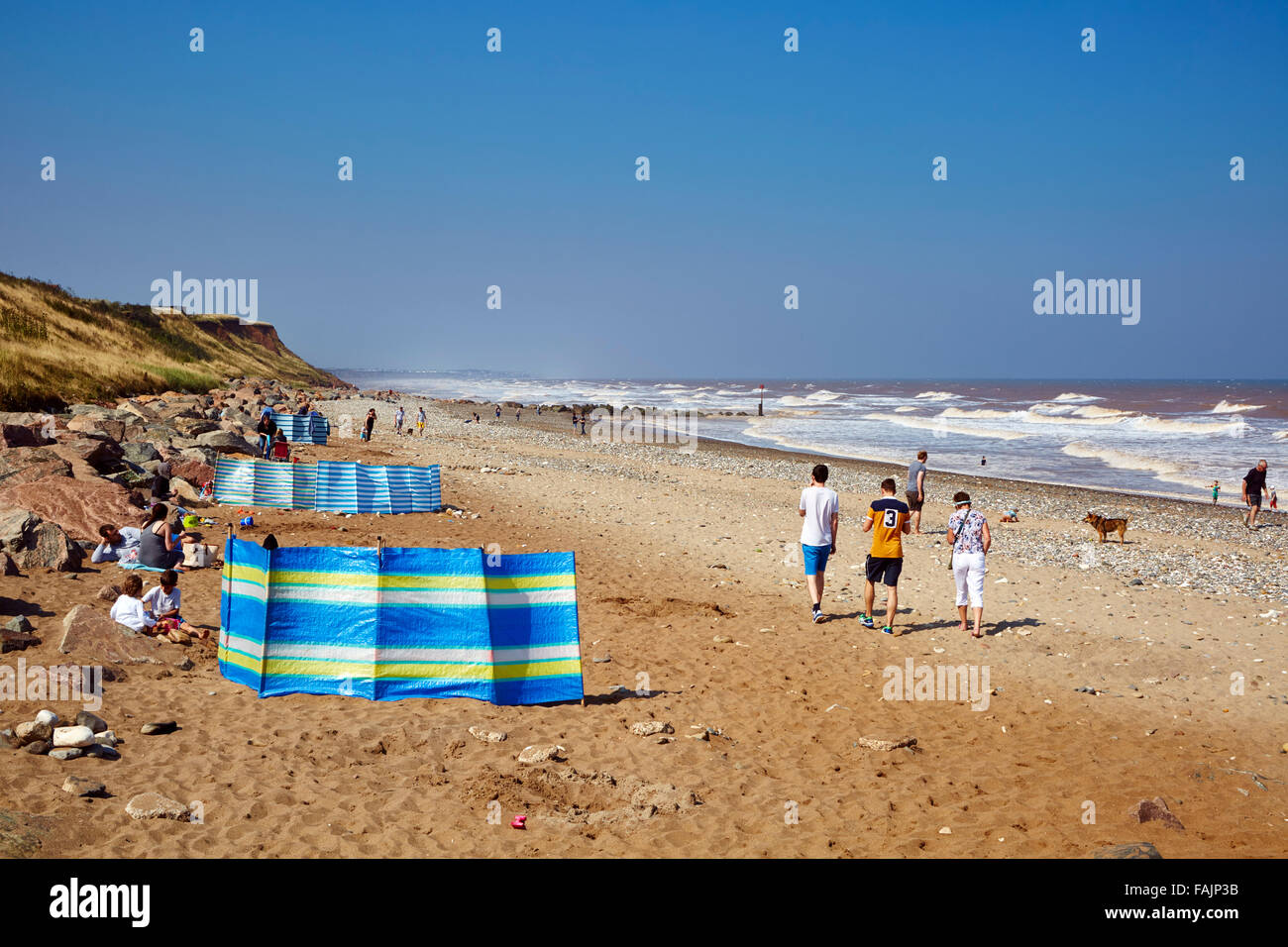 Families enjoy a September day behind wind-breaks on Mappleton Beach with a sea breeze on an sunny day. Copy space - Stock Image