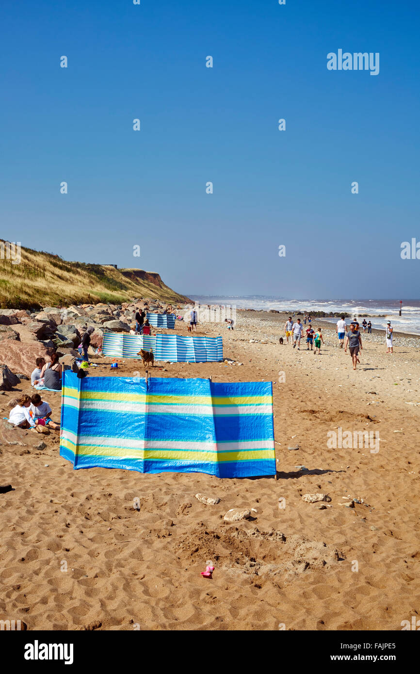 Families enjoy a September day behind wind-breaks on Mappleton Beach with a sea breeze on an sunny day. Copy space Stock Photo