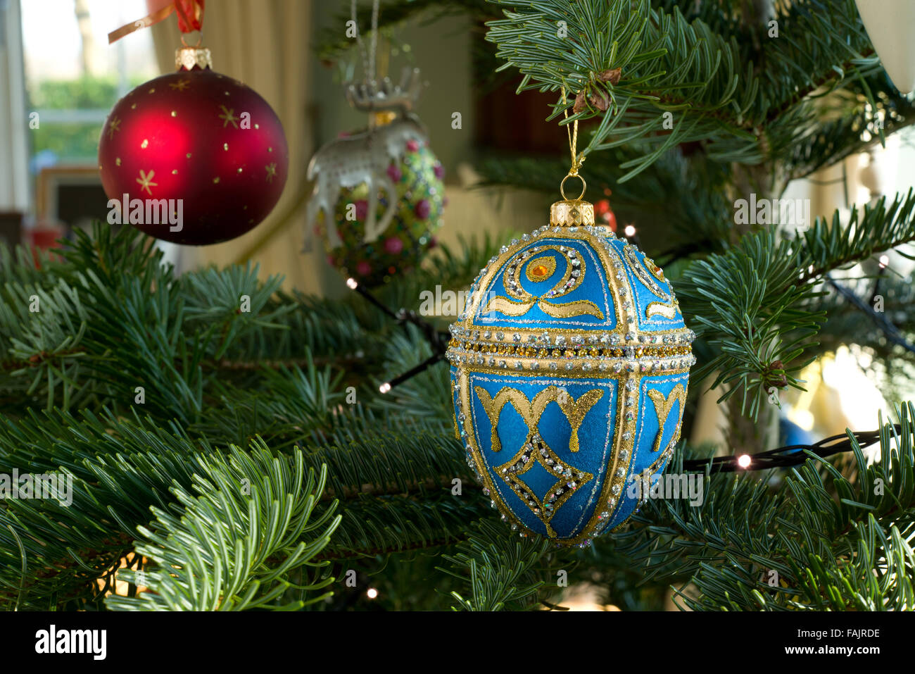 Christmas decorations on a Spruce Christmas Tree. Blue and gold bejeweled egg with other baubles. Stock Photo