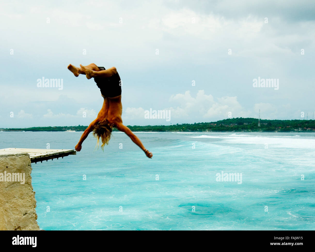 Young man somersaulting in to the sea, Indonesia. Stock Photo