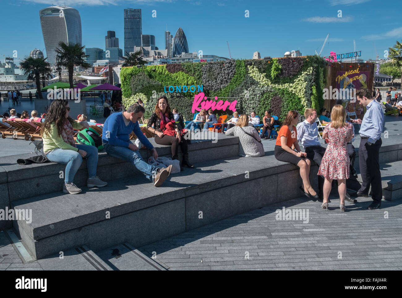 People relaxing and socialising in summer sunshine at London Riviera pop up restaurant, with London skyline in the - Stock Image