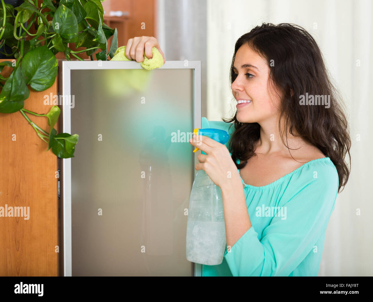dusting furniture. Brunette Woman Dusting Glass Of Furniture At Home