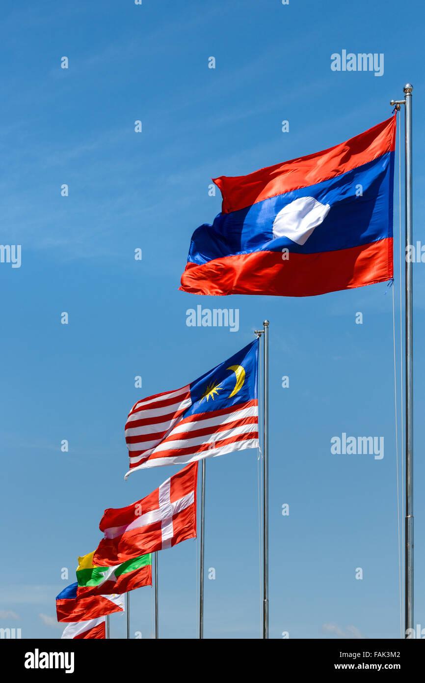 Laotian, Malay, and Danish flag in the wind, blue sky, Sisowath Quay, Phnom Penh, Cambodia - Stock Image
