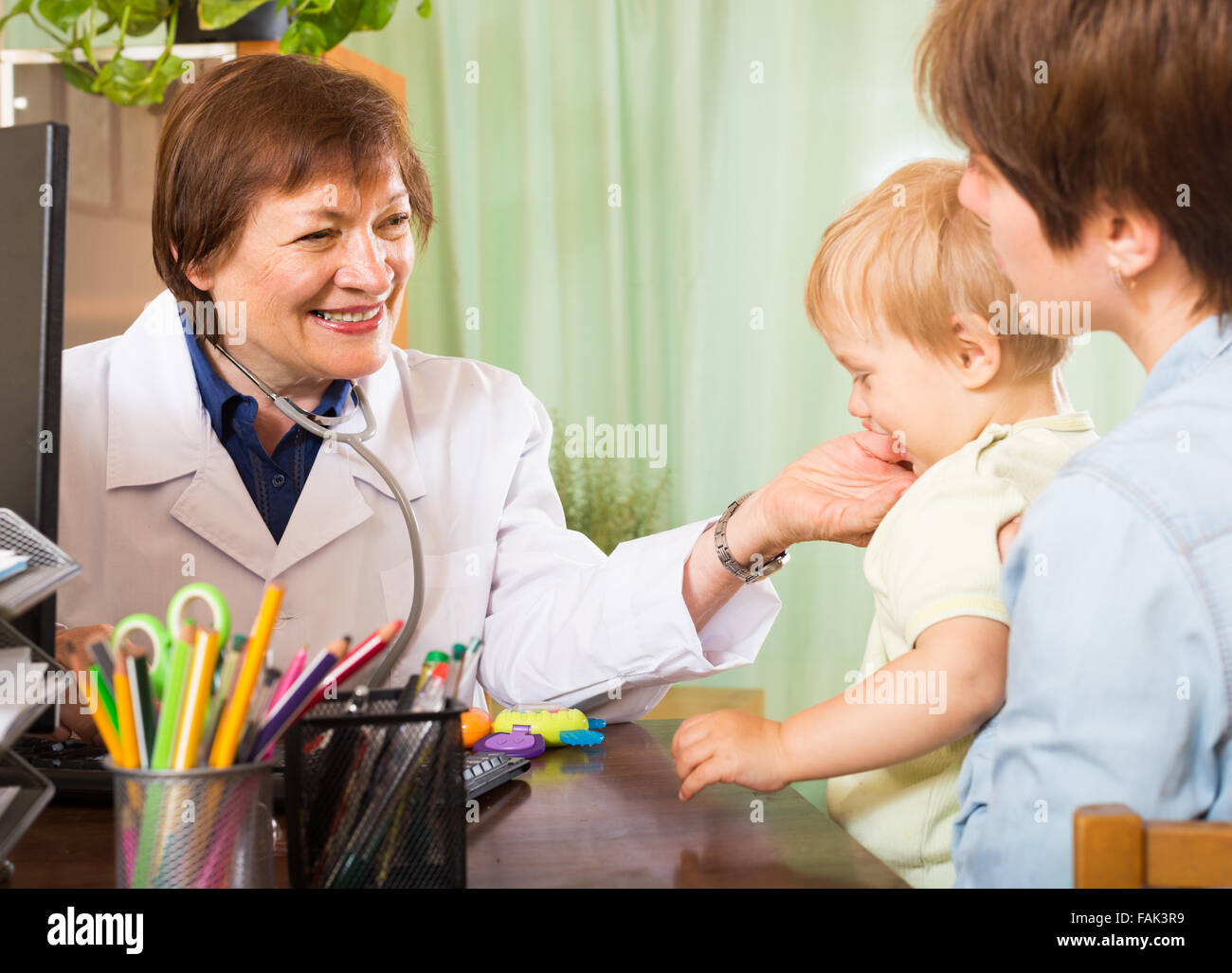 Smiling mature pediatrician doctor talking with mother of baby at clinic office - Stock Image