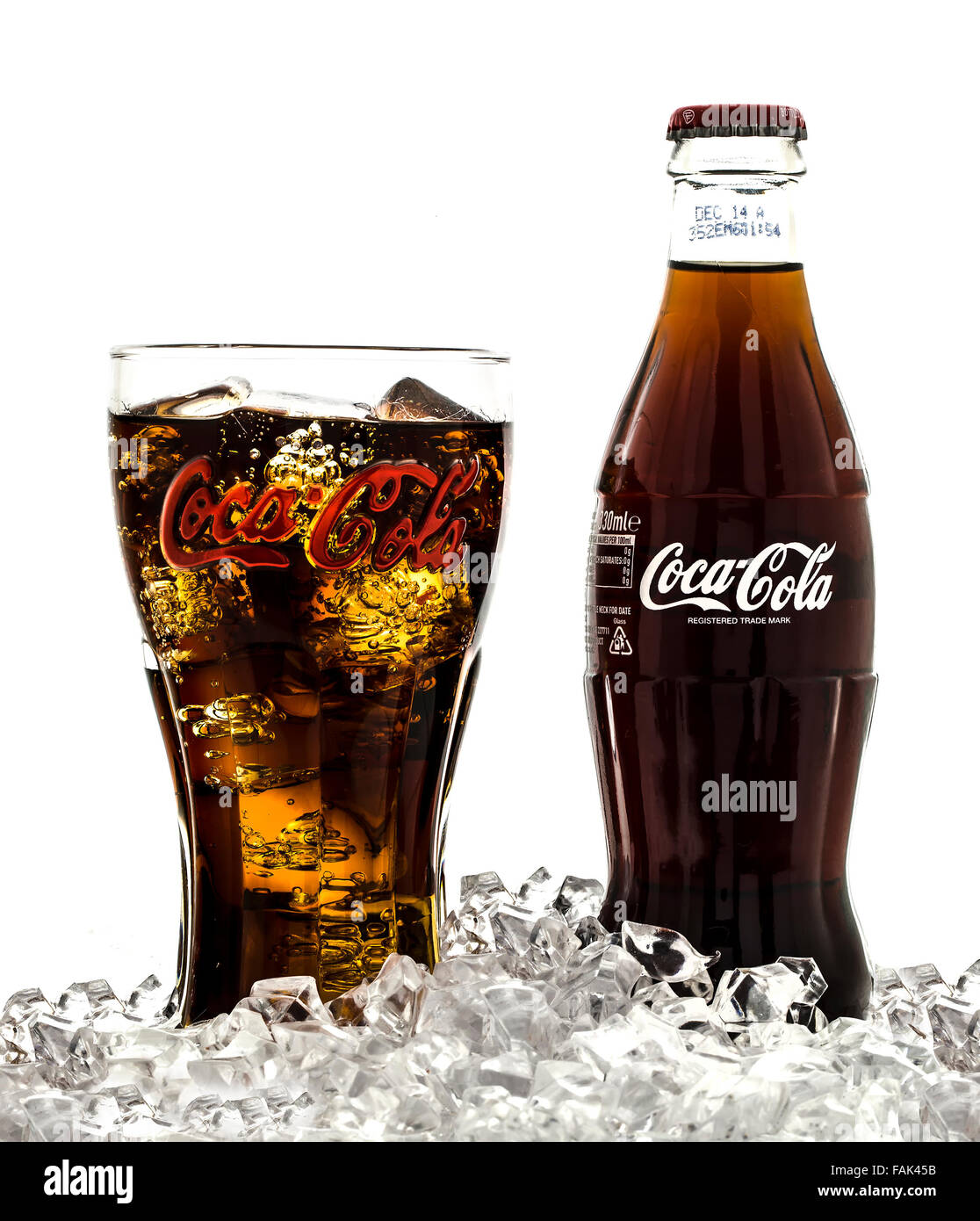 Coca-Cola in Classic Retro  Branded Glass with Classic Bottle on Ice over a white background - Stock Image