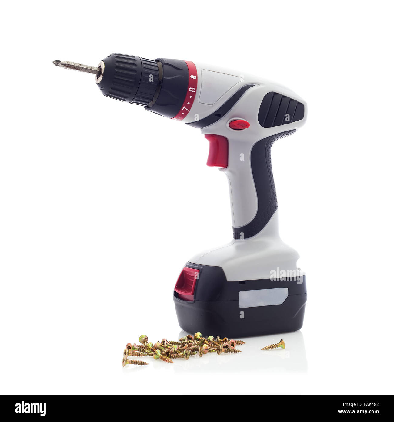 Cordless Drill with Screwdriver Bit and Screws on a White Background - Stock Image