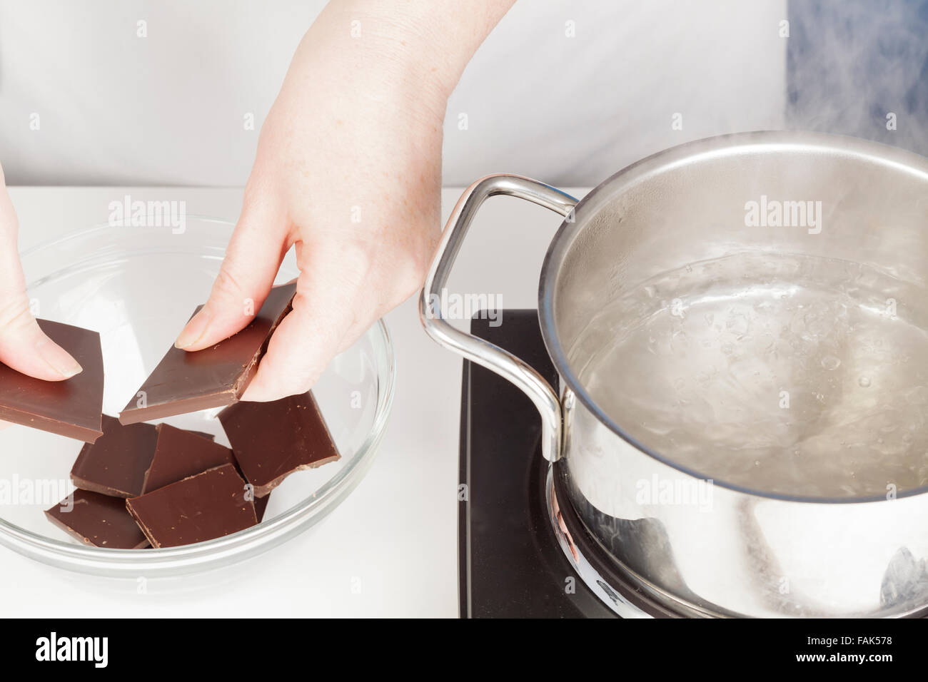 breaking chocolate to melt in bain marie - Stock Image