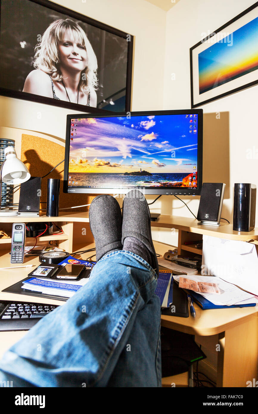 Feet on desk office worker relaxing in front of computer screen legs crossed UK England - Stock Image