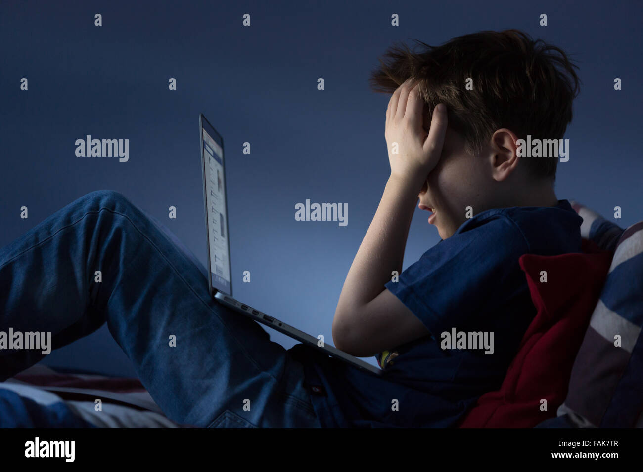 Online bullying Cyber bullying photo of an upset boy in his bedroom looking at hurtful messages on social media - Stock Image