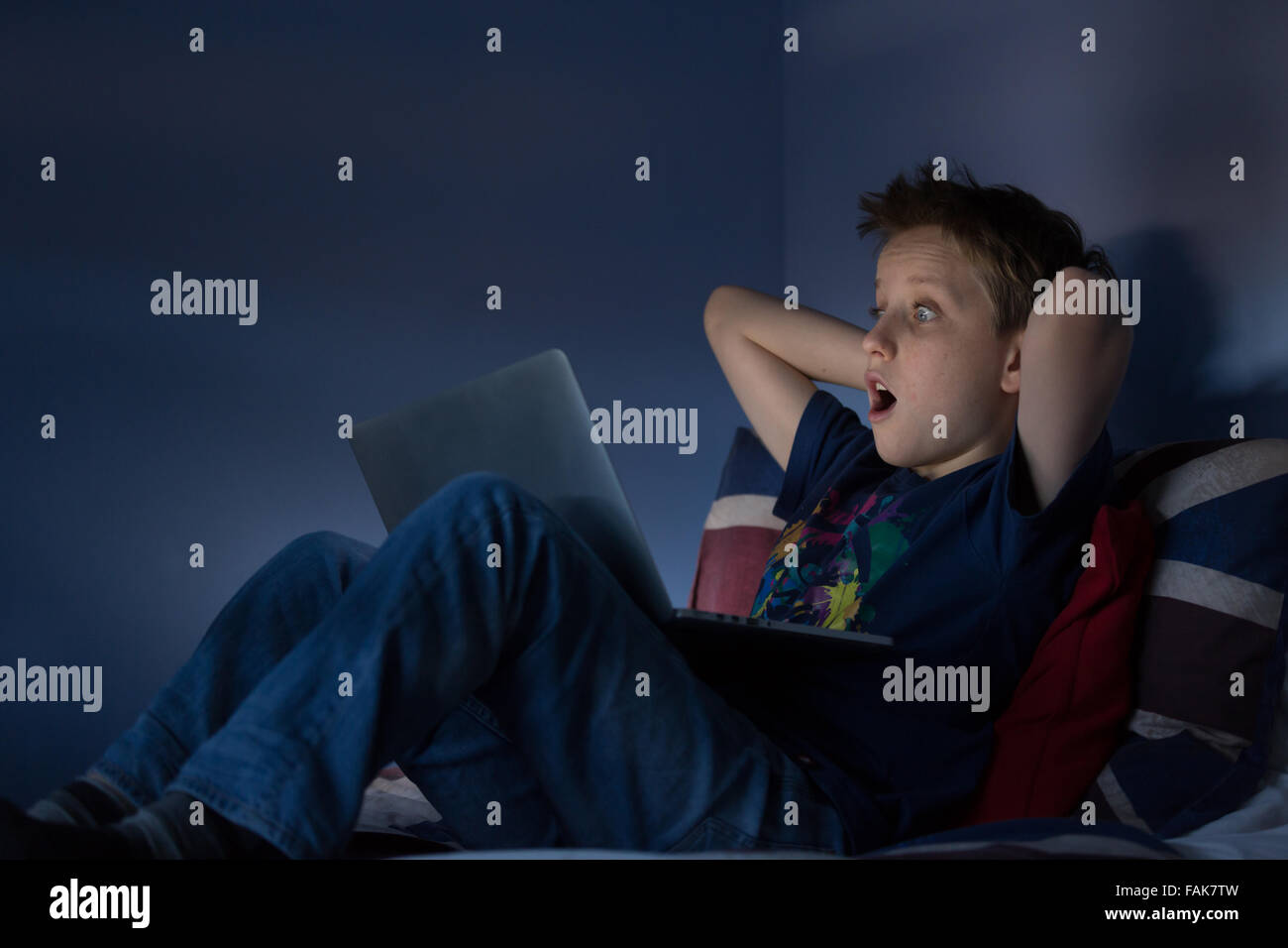 A boy sitting up late in his bedroom looking at the internet shocked at what he is seeing - Stock Image