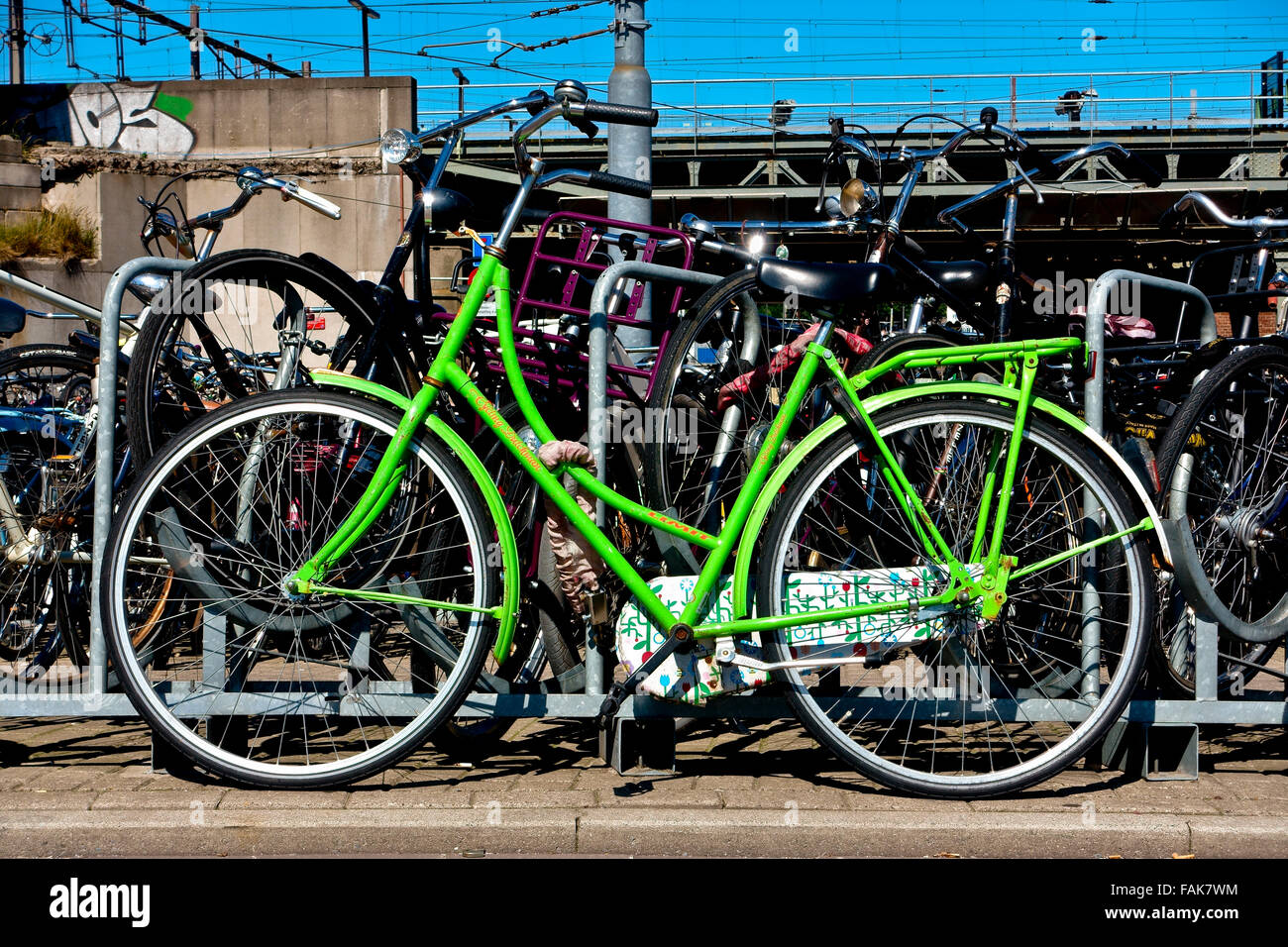 Green bike parked near the railway. Amsterdam, Holland, Netherlands, Europe. Climate change, global warming. Eco - Stock Image
