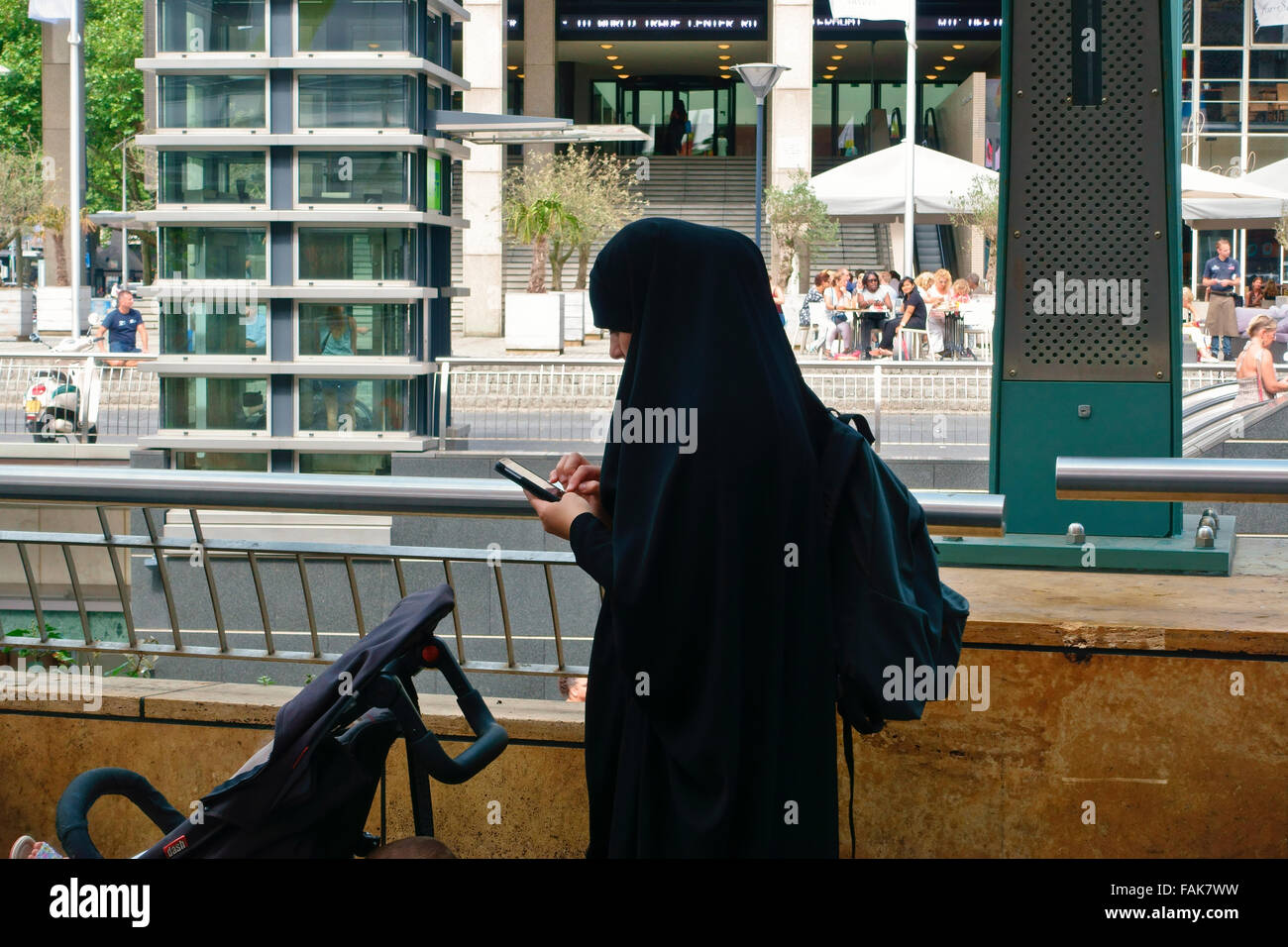 muslim woman wearing burka traditional clothing, using a mobile phone. Shopping mall. - Stock Image