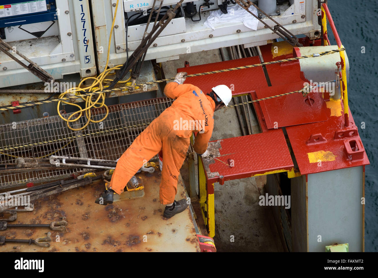Container ship crew member works on the deck of Utrillo