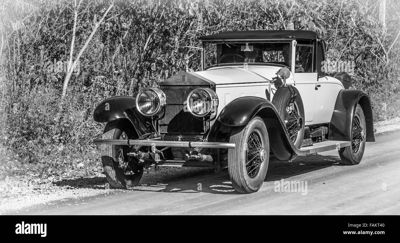 An old antique car from a century ago drives down a country road on ...
