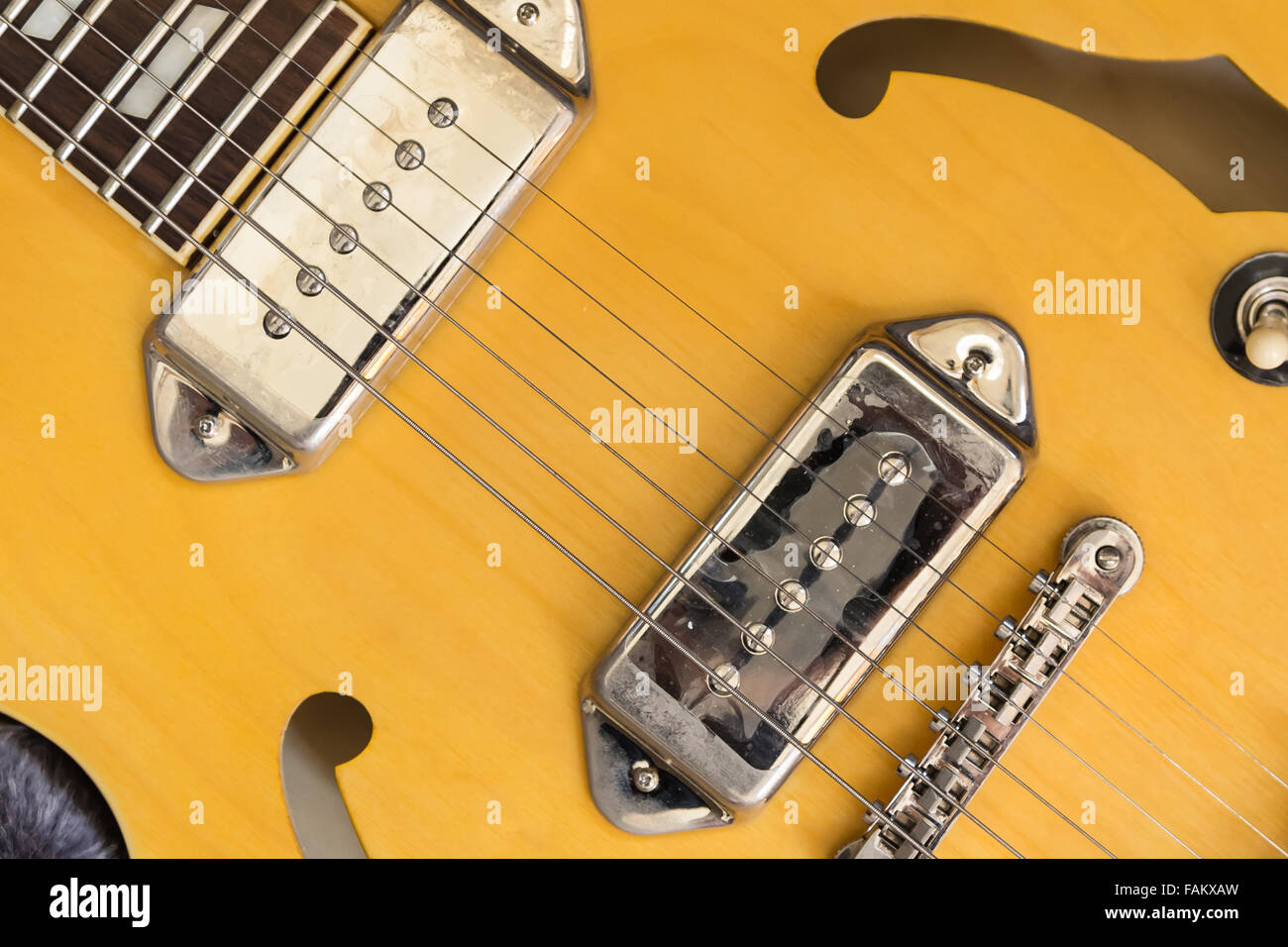 It\'s a part of body of a yellow electric guitar which made from wood ...