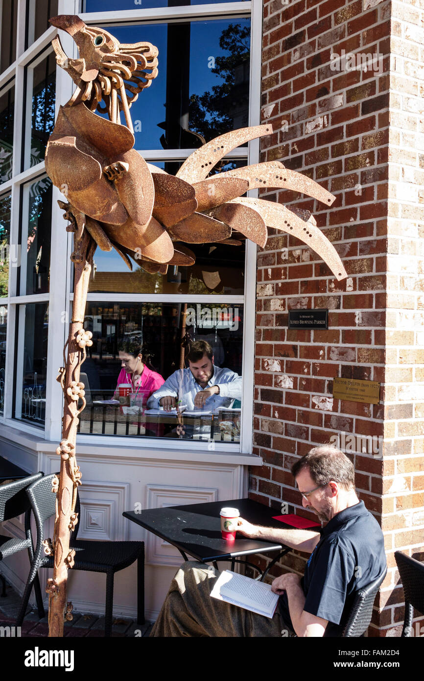 Gainesville Florida SE 1st Street Starbucks Coffee cafe alfresco man woman couple art metal sculpture rooster Stock Photo