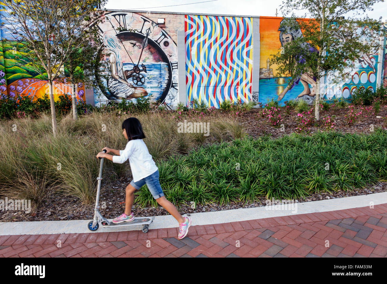 Gainesville Florida SW Depot Avenue wall mural art Asian girl riding scooter - Stock Image