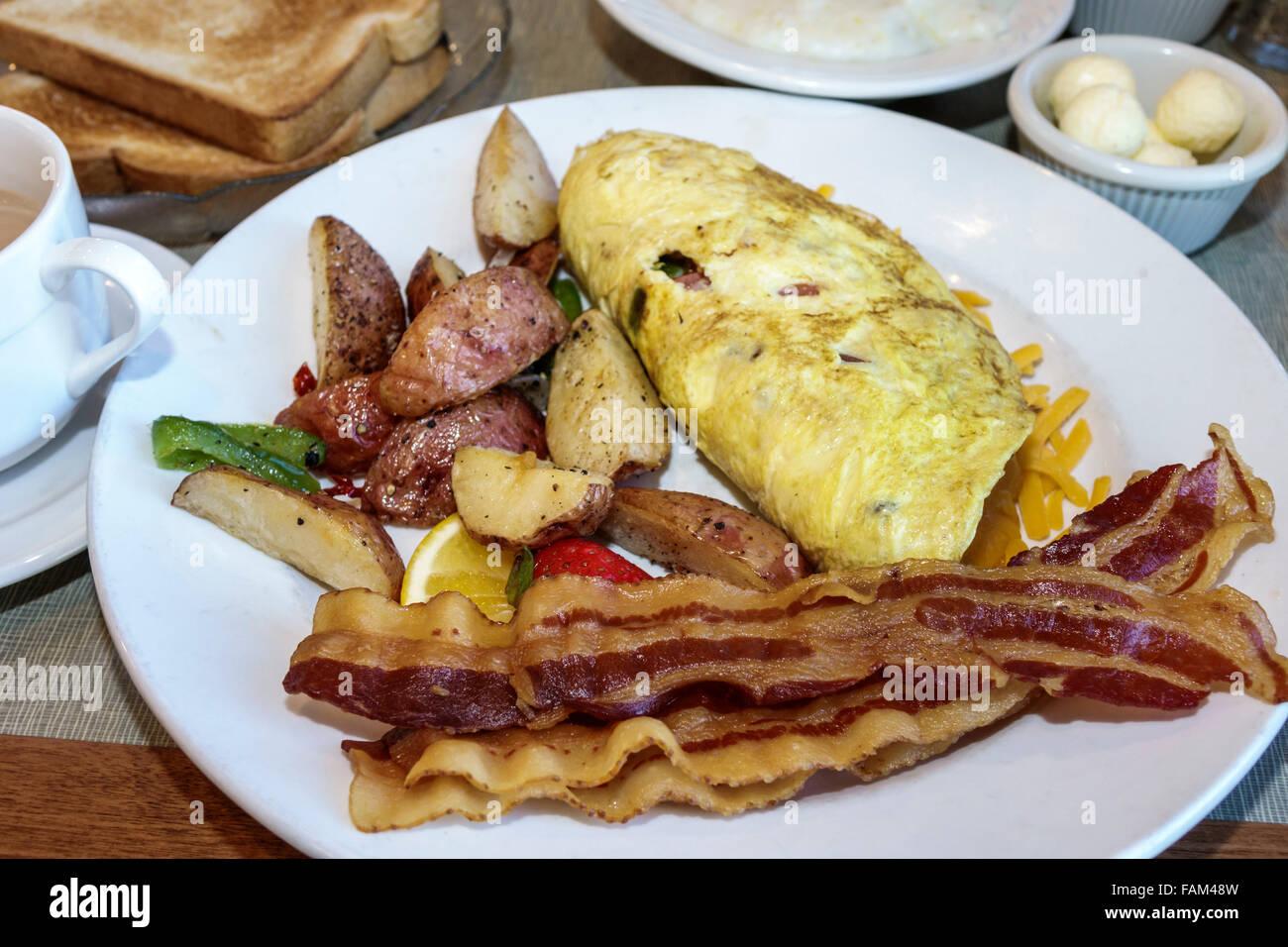 Florida Crystal River Plantation on Crystal River Resort hotel restaurant inside breakfast food omelet bacon potatoes - Stock Image
