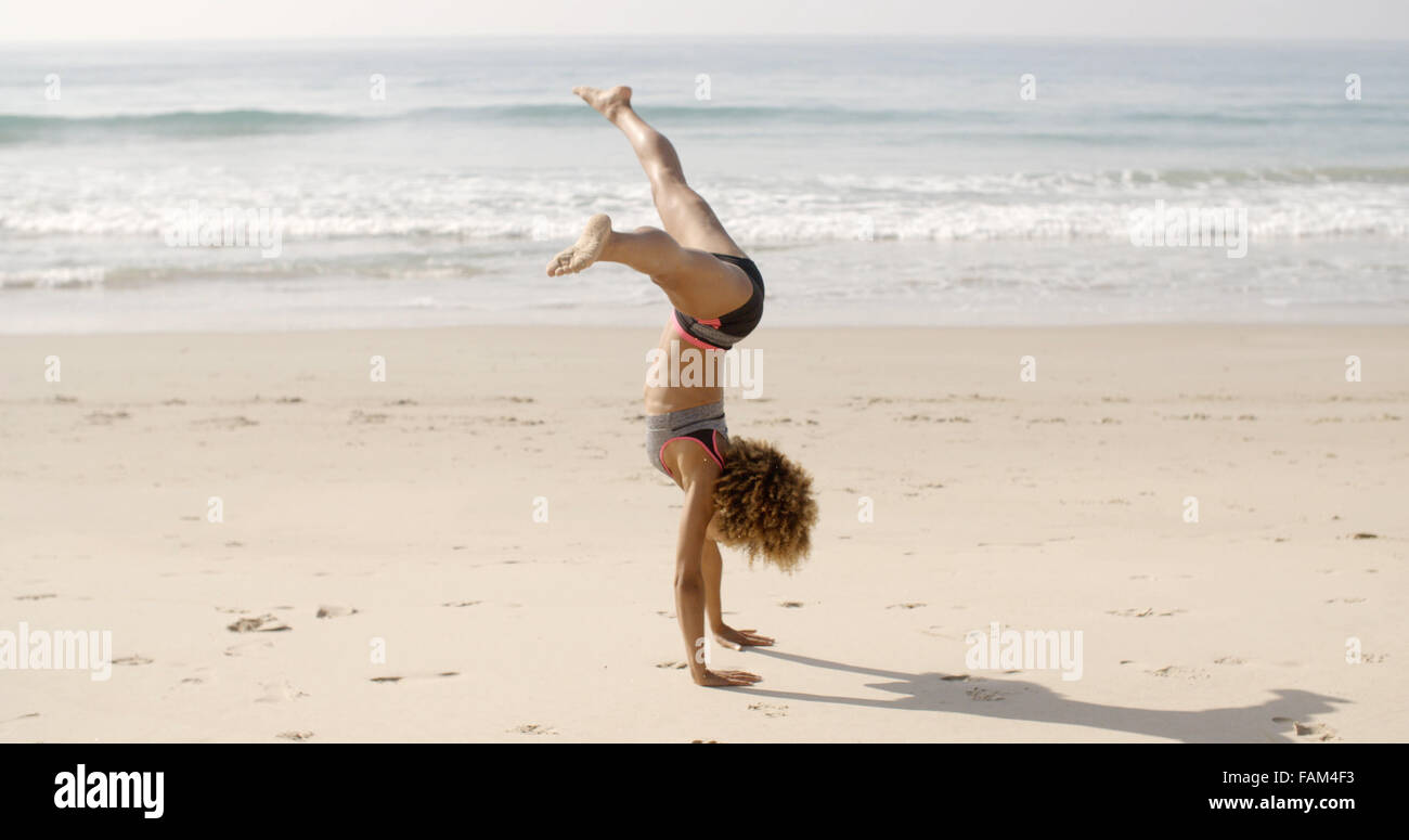 Young Woman Doing Cartwheel On Beach - Stock Image