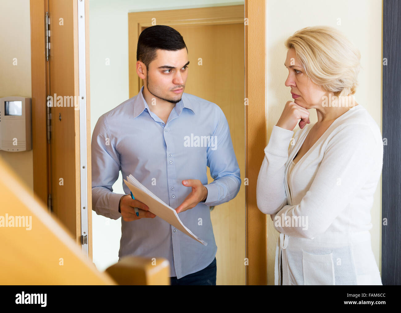 Collector is trying to get the arrears from mature unhappy woman at home door Stock Photo