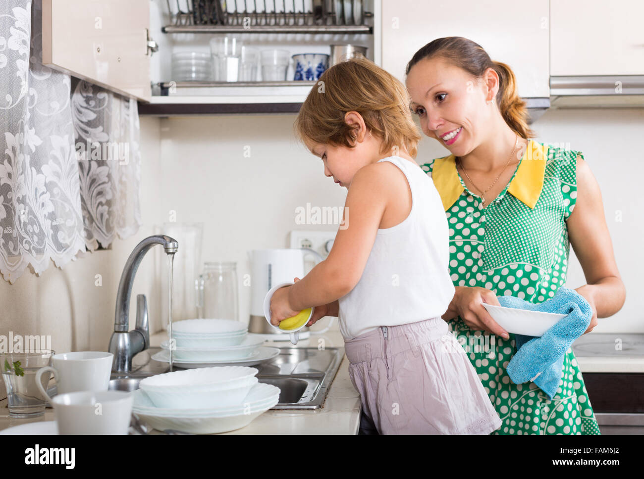 Baby girl helping mother washing dishes in the kitchen. Focus on ...