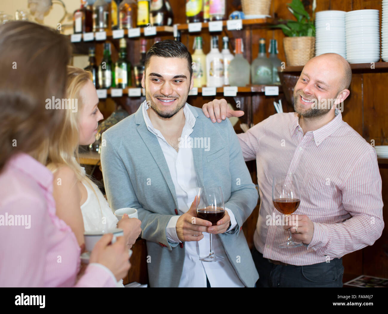 Casual acquaintance of smiling young adults at bar. Selective focus - Stock Image