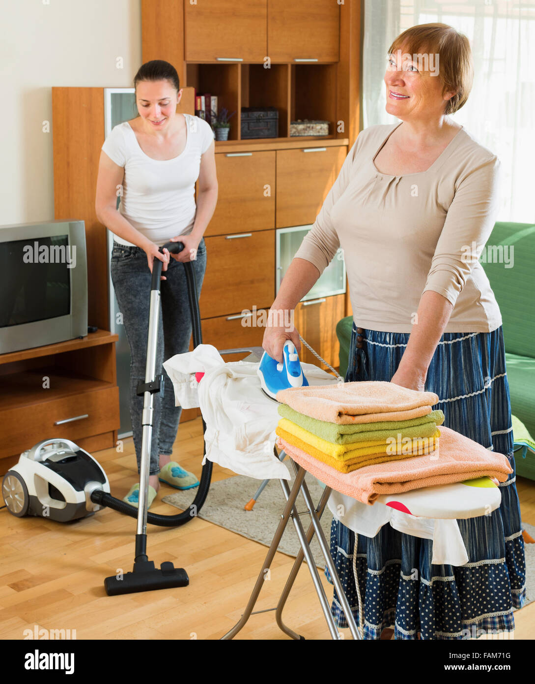 Mature Woman Ironing Clothes And Her Daughter Help Cleaning Home