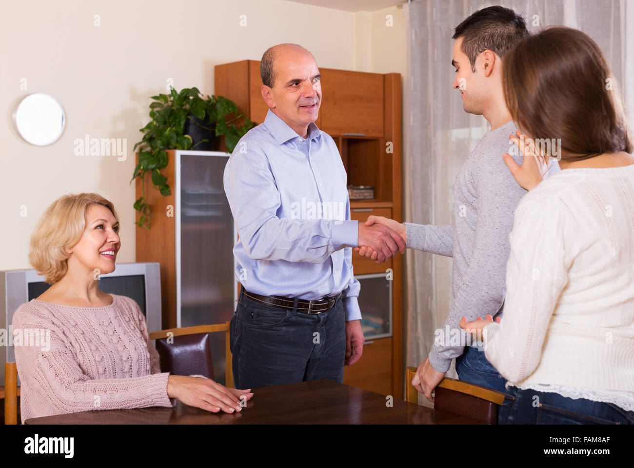 Girl showing his future husband to smiling parents - Stock Image