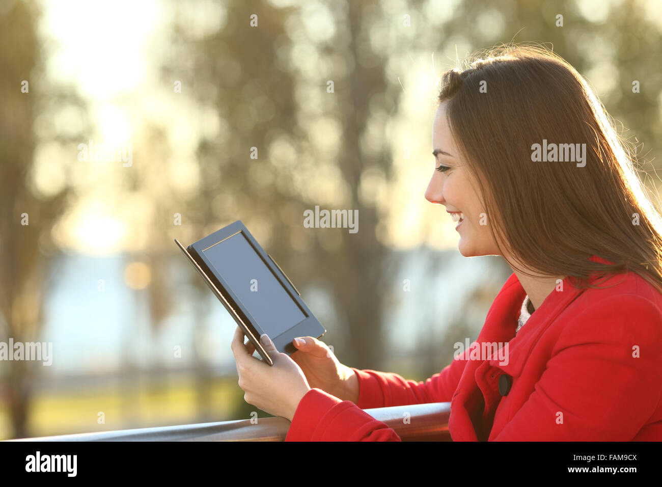 Woman reading an ebook in a balcony at sunset in winter - Stock Image