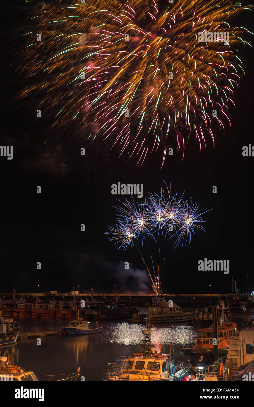 New Year Eve firework display at Ramsgate Royal Harbour with the commercial fleet in the foreground. Stock Photo