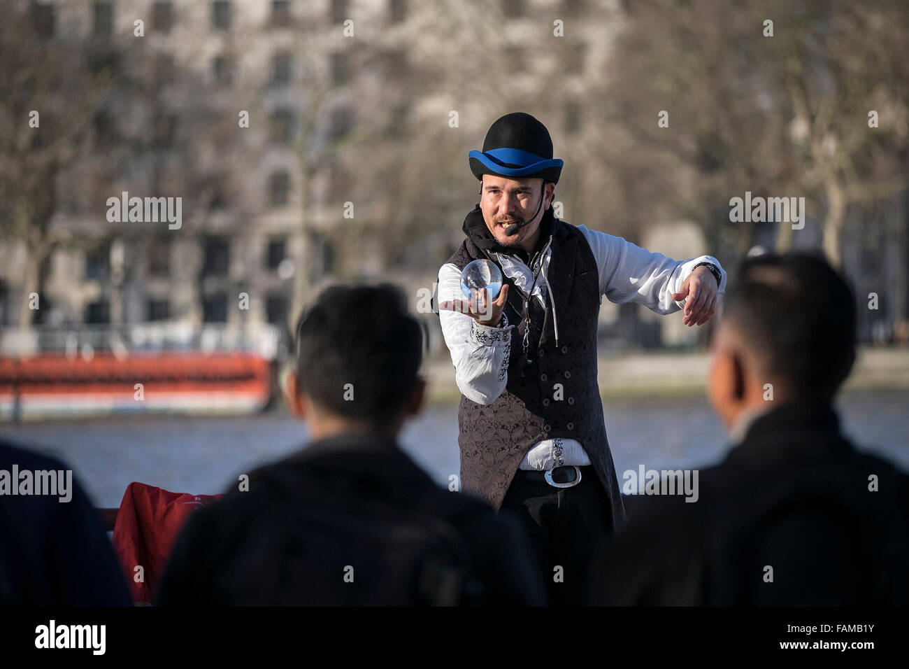 On the South Bank in London a busker entertains the public with a magic trick. - Stock Image