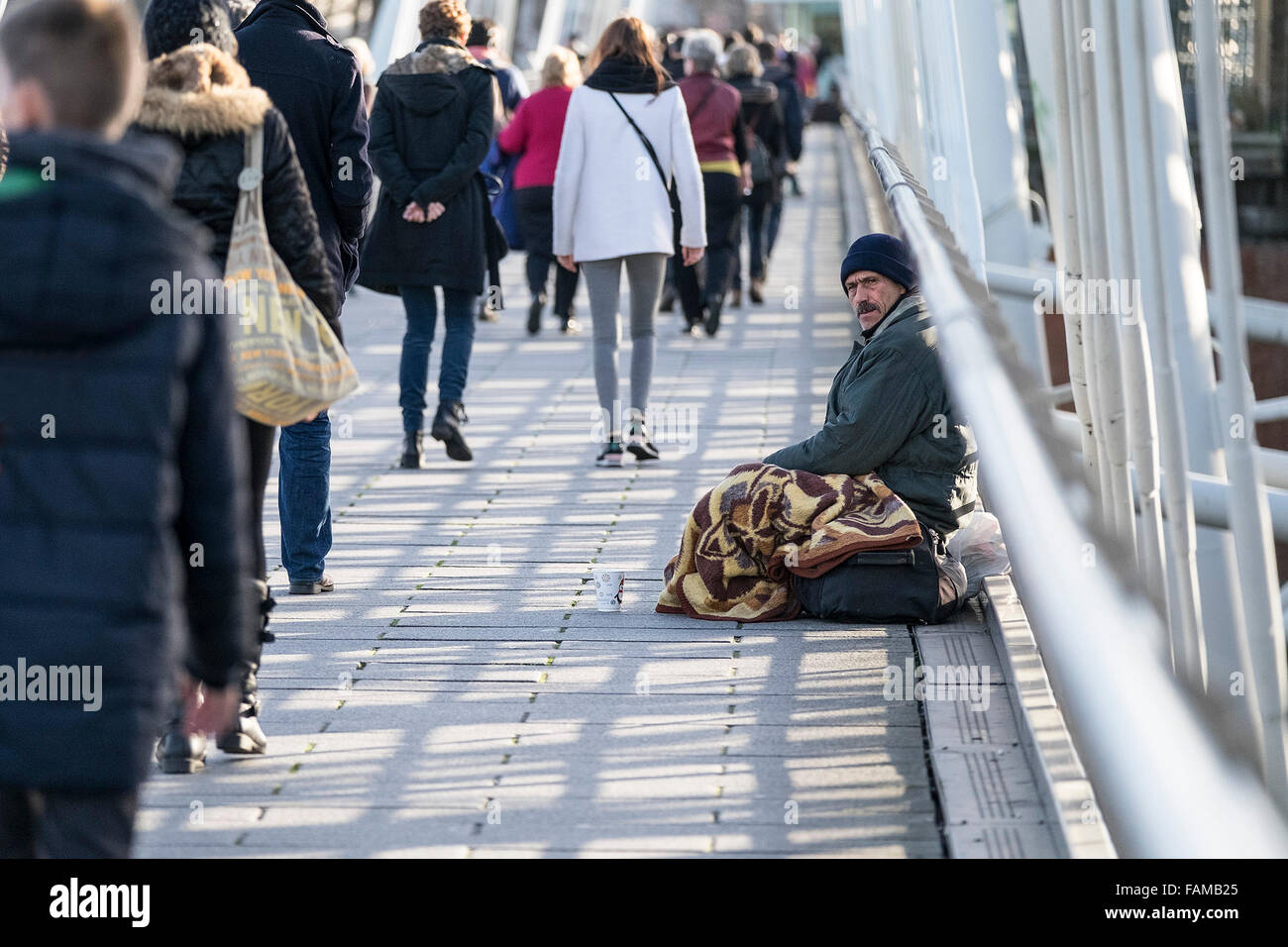 People walking past a homeless man begging on Hungerford Bridge in London. - Stock Image