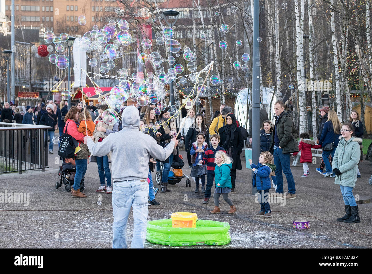 A street entertainer creates bubbles to amuse children and their parents on the South Bank in London. - Stock Image